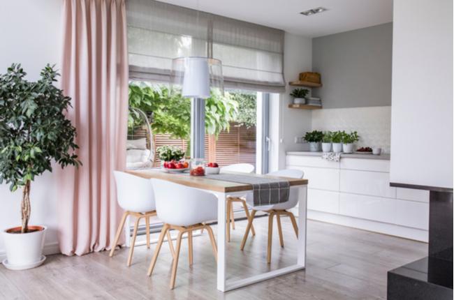 tons romanos cinza e uma cortina rosa em grandes janelas de vidro em uma cozinha moderna e sala de jantar interior com uma mesa de madeira e cadeiras brancas