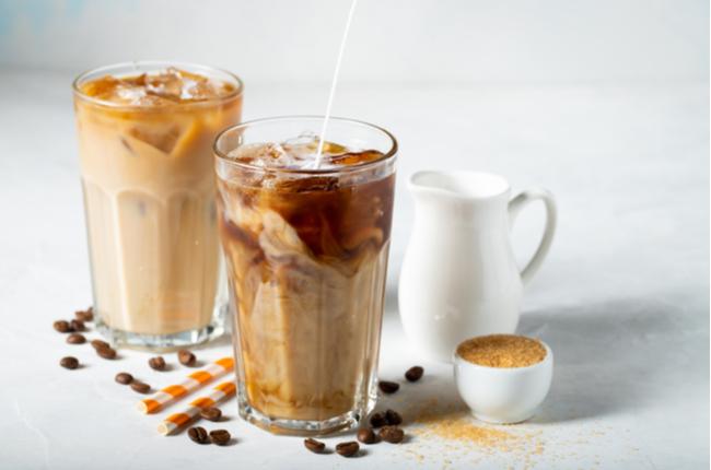 Café gelado em um copo alto com creme derramado sobre e grãos de café. Bebida de verão fria em um fundo azul claro