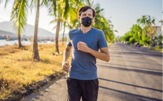 Homem com máscara praticando exercício físico