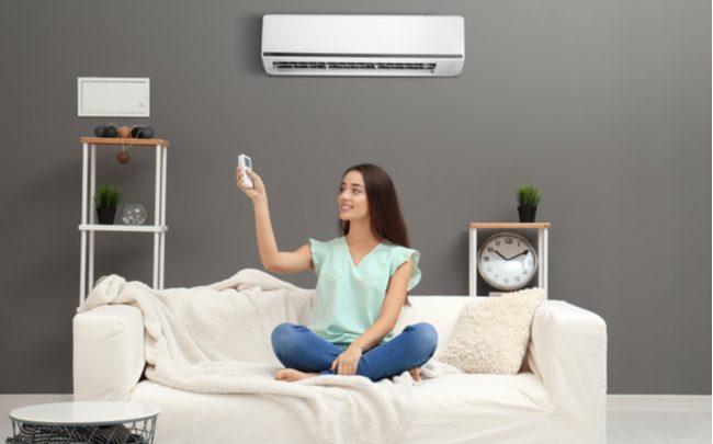 mulher utilizando ar-condicionado na sala