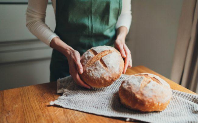 pão caseiro assado segurado por uma mulher