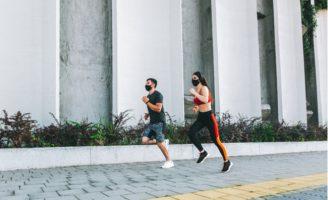 casal saudável praticando exercício com máscara