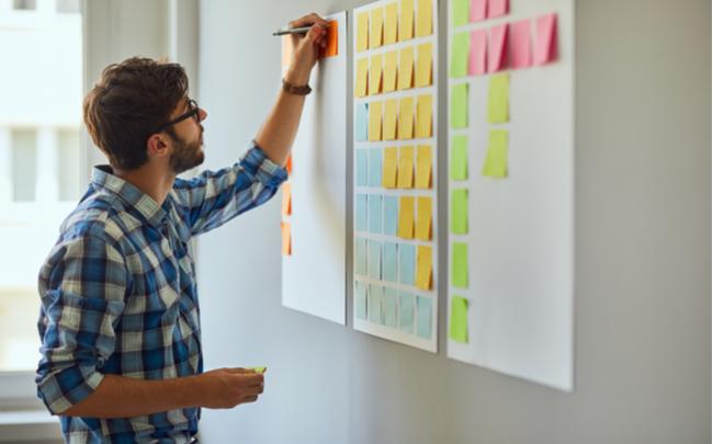 Homem criando modelo de negócio através de post its - SEPAC