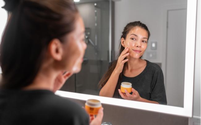 Mulher em frente a um espelho de um banheiro com ótima iluminação
