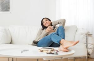Mulher sentada no sofá com uma xícara para relaxar - UNIVERSO DO CUIDADO