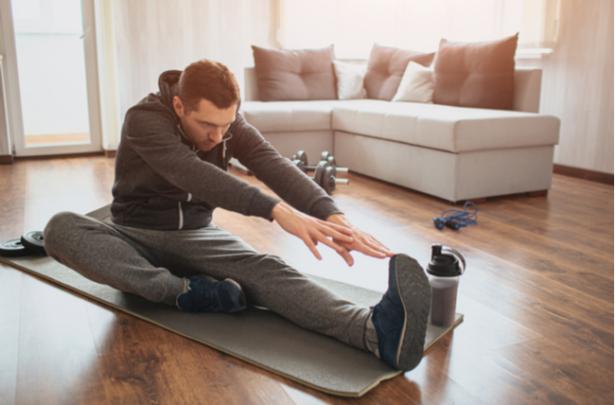 Homem praticando alongamento em casa